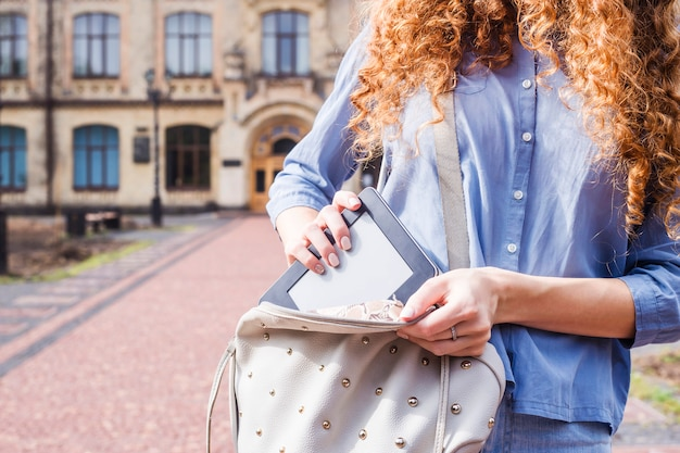 Ein mädchen mit langen lockigen haaren zieht ein e-book aus ihrem rucksack