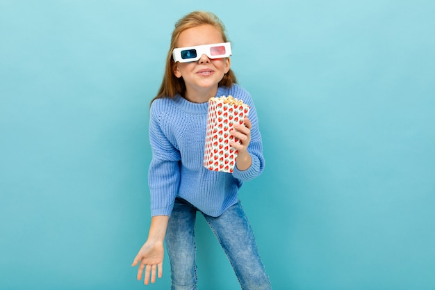 Ein mädchen mit make-up und langen braunen haaren, 3d-brille sieht film oder cartoon mit popcorn