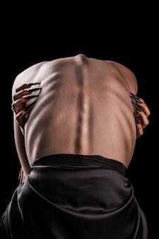 Ein mädchen mit nacktem rücken, starker dünnheit und hervorstehenden rippen