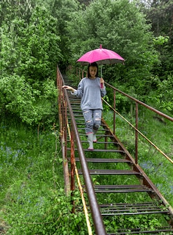 Ein mädchen mit regenschirm spaziert bei regenwetter im wald