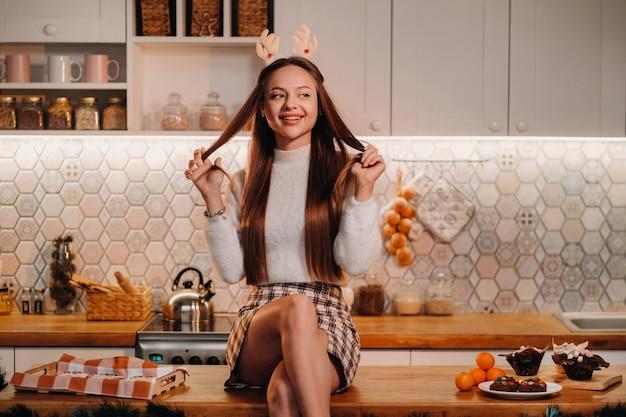 Ein mädchen mit rentierhörnern zu weihnachten sitzt auf dem küchentisch und lächelt. frau im neuen jahr in der küche