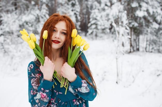Ein mädchen mit roten haaren hält einen strauß gelber tulpen auf einer winterlandschaft