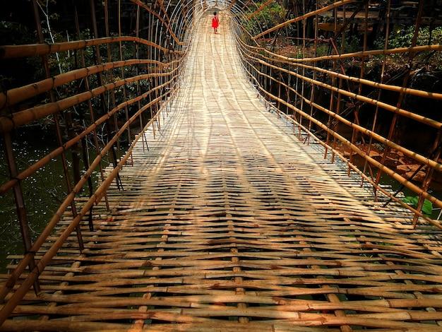 Ein mädchen mit roter klage gehend auf bambusbrücke