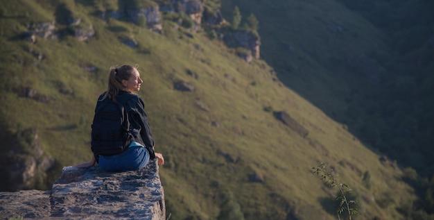 Ein mädchen mit rucksack steht am rand einer klippe. reise durch die berge
