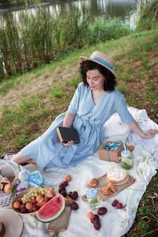 Ein mädchen mit strohhut und einem langen blauen kleid sitzt auf einer weißen decke mit obstgebäck und korb