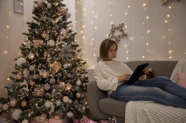 Ein mädchen mit tablet auf dem sofa in einem festlich geschmückten wohnzimmer