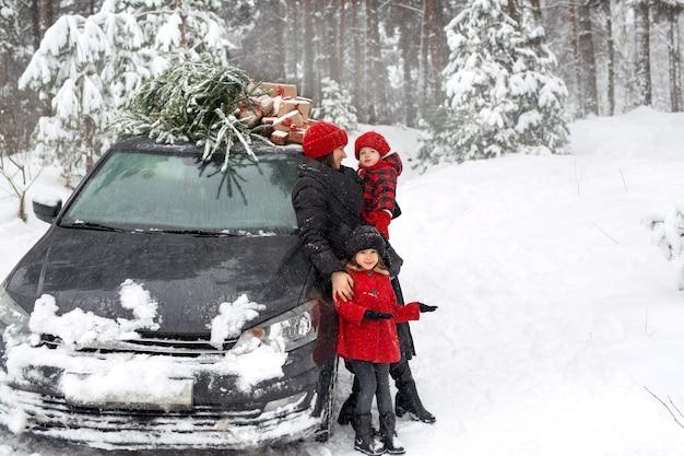 Ein mädchen neben der mutter und ein auto mit einem weihnachtsbaum zeigt mit der hand beiseite auf den kopierraum