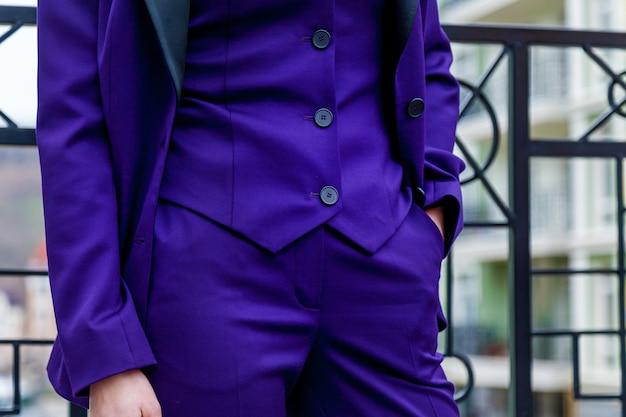 Ein mädchen posiert für den fotografen im blauen hosenanzug auf der straße