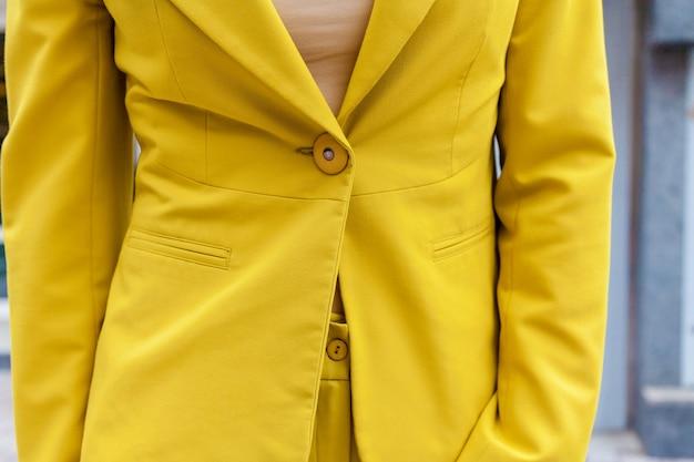 Ein mädchen posiert für den fotografen im gelben hosenanzug mit einer bunten handtasche an der grünen wand