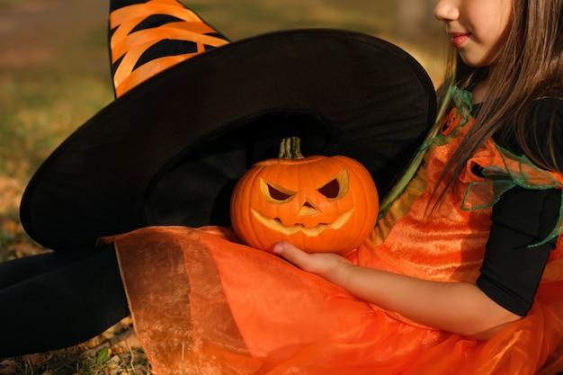 Ein mädchen probiert an einem unheimlichen kürbis einen großen schwarzen hexenhut an halloween an