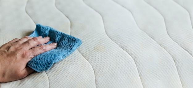 Ein mädchen reinigt eine matratze das konzept eines sauberen hauses