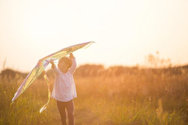 Ein mädchen rennt mit einem drachen auf ein feld und lernt, ihn zu starten. outdoor-entertainment im sommer, natur und frische luft. kindheit, freiheit und sorglosigkeit. ein kind mit flügeln ist ein traum und eine hoffnung.