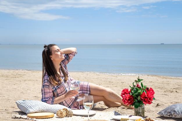 Ein mädchen ruht sich am strand aus. ein romantisches picknick am sandstrand. das konzept der sommerferien.