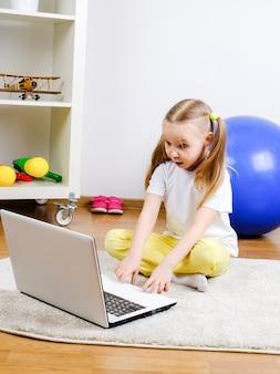 Ein mädchen schaut auf den computer. das kind ist überrascht.