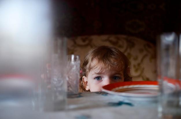 Ein mädchen schaut hinter einem tisch hervor