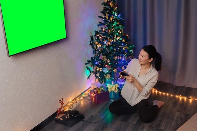 Ein mädchen sitzt auf dem boden neben dem neujahrsbaum, hält einen joystick in den händen, schaut auf den bildschirm und spielt auf der konsole.