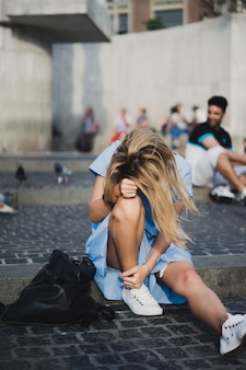Ein mädchen sitzt auf dem dam square. amsterdam.