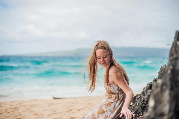 Ein mädchen sitzt auf einem felsen am strand von boracay