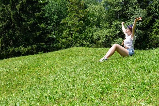 Ein mädchen sitzt auf einem hintergrund von bergen auf dem grünen rasen und genießt die sonne.