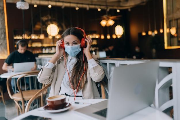 Ein mädchen sitzt in einem café mit kopfhörer-coronavirus-ausbruch