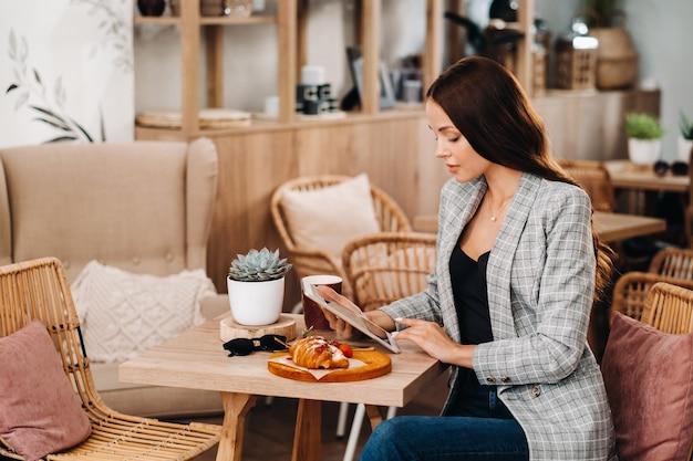 Ein mädchen sitzt in einem café und schaut auf eine tablette, ein mädchen in einem café lächelt, fernarbeit.