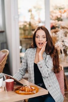 Ein mädchen sitzt in einem café und schaut auf eine tablette, ein mädchen in einem café lächelt,