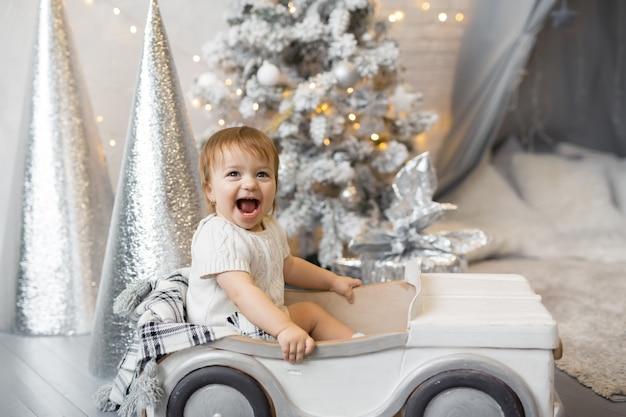 Ein mädchen sitzt in einem spielzeugauto im zimmer mit weihnachtsschmuck