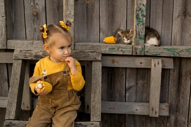 Ein mädchen sitzt mit einem kätzchen auf einer holztreppe und isst mais