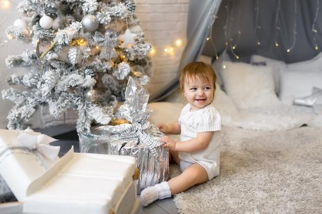 Ein mädchen sitzt mit einem weihnachtsgeschenk in einer silbernen hülle eines kinderzimmers