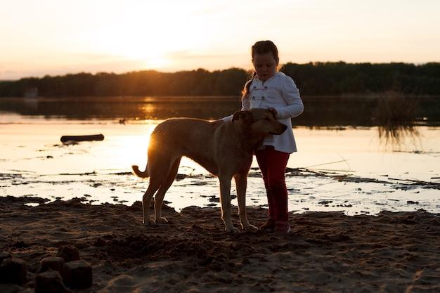 Ein mädchen spielt mit einem hund an einem sandstrand am fluss bei sonnenuntergang.