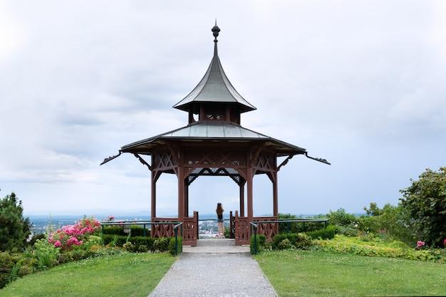 Ein mädchen steht auf der aussichtsplattform im pavillon und fotografiert die schöne aussicht.