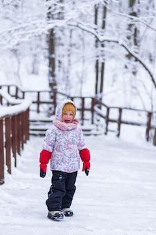 Ein mädchen steht in der nähe des geländers im winterwald