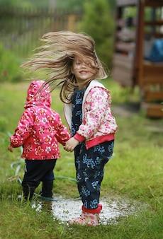 Ein mädchen tanzt in einer pfütze, ihr haar fliegt das mädchen trägt gummistiefel und eine jacke