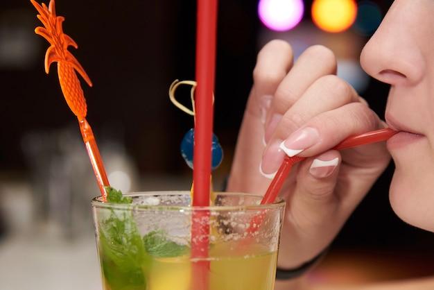 Ein mädchen trinkt einen cocktail an der bar.