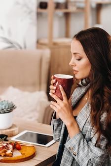 Ein mädchen trinkt kaffee in einem café, schöne haare eines mädchens.