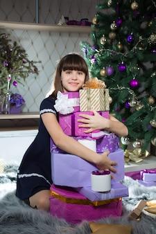 Ein mädchen umarmt einen berg von geschenken in einem raum, der für das neue jahr eingerichtet ist