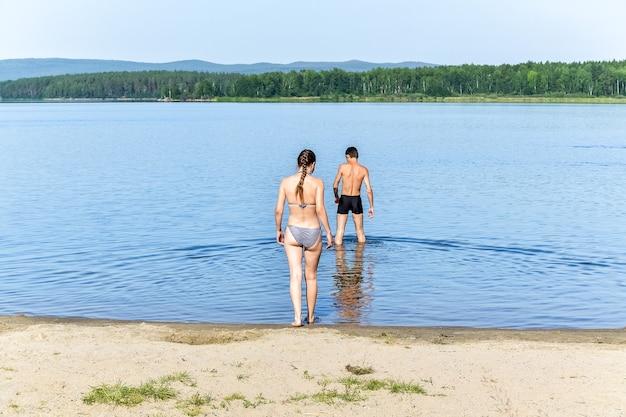 Ein mädchen und ein junge gehen im see schwimmen