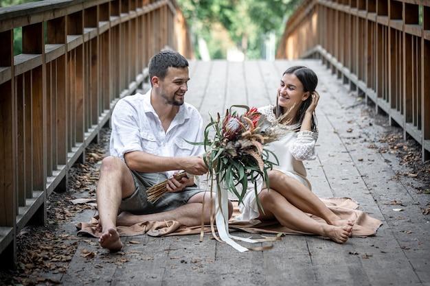 Ein mädchen und ein junger mann sitzen auf der brücke und genießen die kommunikation, ein date in der natur, eine liebesgeschichte.