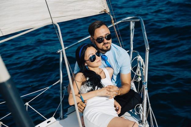 Ein mädchen und ein mann mit asiatischem aussehen sitzen auf dem deck der yacht und umarmen sich. ein paar hände berühren sich.