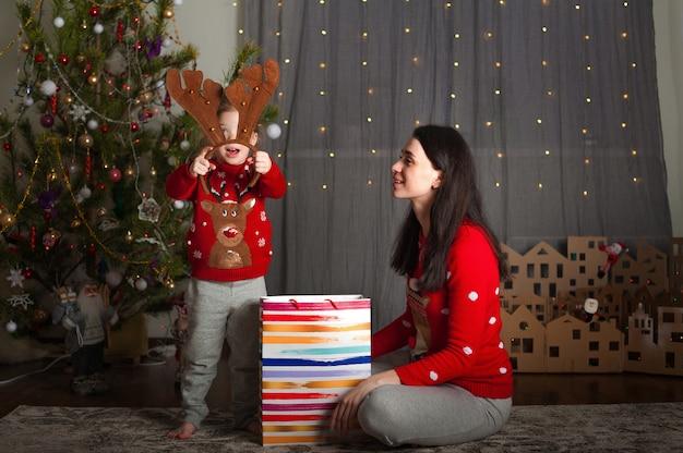 Ein mädchen und eine mutter schauen sich geschenke an, umarmen, küssen den weihnachtsbaum zu hause für das neue jahr. bleib zu hause für den urlaub.