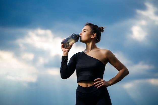 Ein mädchen von europäischem aussehen mit einem sportlichen build in einem schwarzen top und schwarzen leggings vor blauem himmel. sie trinkt wasser aus einer flasche. gesunder lebensstil, athletisches brunettemädchen. motivation zum sport
