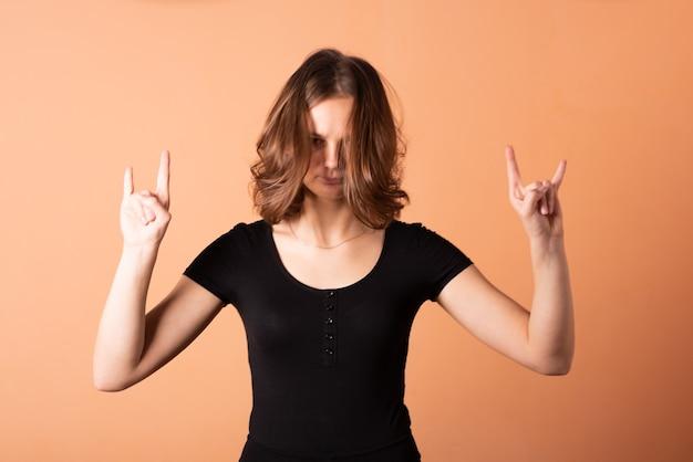Ein mädchen zeigt eine rockerziege auf einem hellorangefarbenen hintergrund. für jeden zweck.