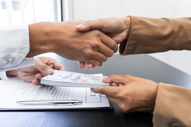 Ein männlicher agent, der seinem gierigen partner geld gibt, um im gegenzug einen gefallen zu bekommen.