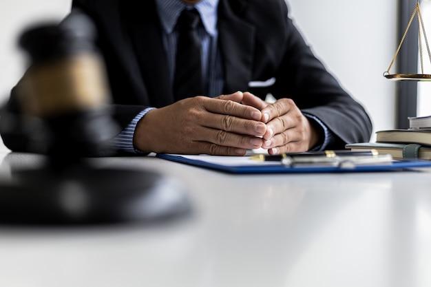 Ein männlicher anwalt sitzt in seinem büro auf einem tisch und schlägt mit einem kleinen hammer vor gericht auf den schreibtisch des richters. und gerechtigkeitsskalen entwerfen anwälte einen vertrag, den der mandant mit dem angeklagten zur unterzeichnung verwenden soll