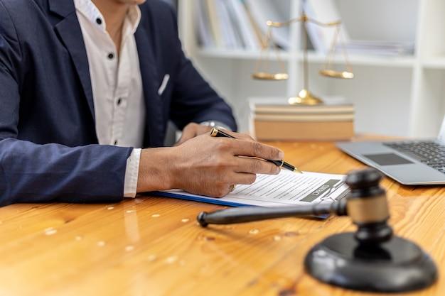 Ein männlicher anwalt unterschreibt mit einem mandanten in einem betrugsfall eine plädoyer-vereinbarung, in dem der mandant eine klage gegen einen mitarbeiter eines unternehmens eingereicht hat, das den betrug begeht. konzept für betrugsstreitigkeiten.