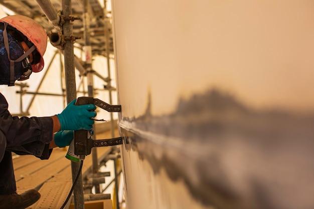 Ein männlicher arbeiter bei hochtest-stahltank-stumpfschweiß-overlay-kohlenstoff-schalenplatte des lagertankölhintergrunds weißer kontrast des magnetfeldtests