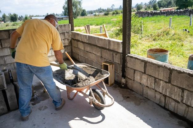 Ein männlicher arbeiter, der eine wand mit brisenblöcken baut