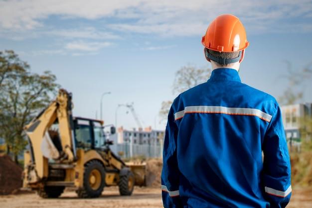 Ein männlicher arbeiter in uniform, der am straßenrand arbeitet und eine neue autobahn baut