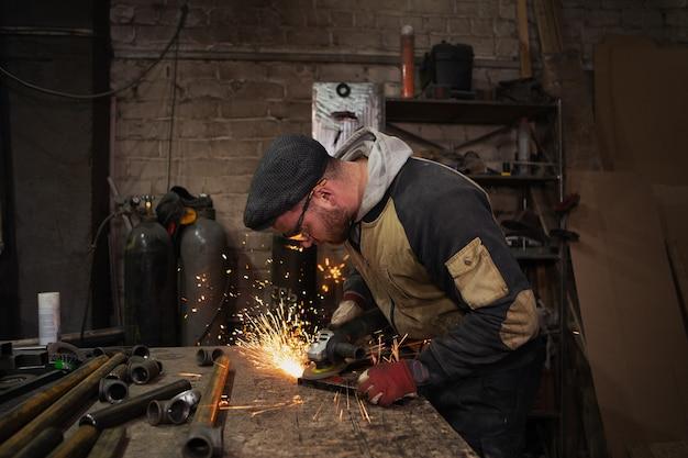 Ein männlicher arbeiter schneidet metall mit einem handschleifer, helle funken fliegen unter der säge in alle richtungen hervor.