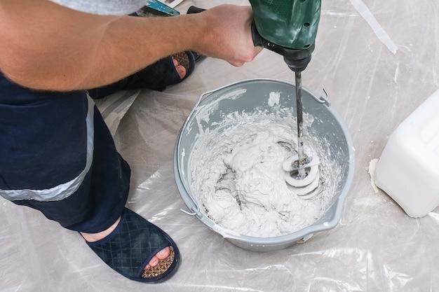 Ein männlicher arbeiter verteilt die kittmischung und glättet die wand.